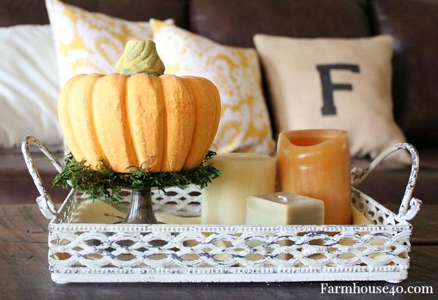 pumpkin and candles create a fall vignette